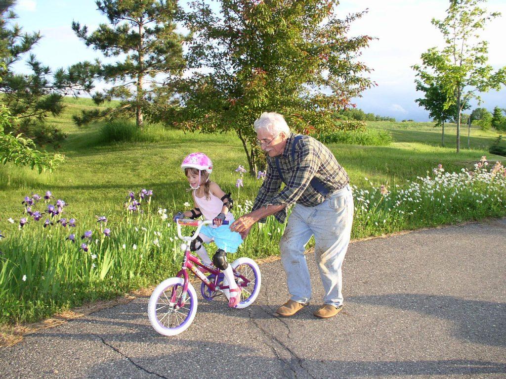 dziadek uczy wnuka jazdy na rowerze
