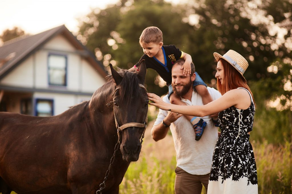 dziecko z rodzicami głaszcze konia