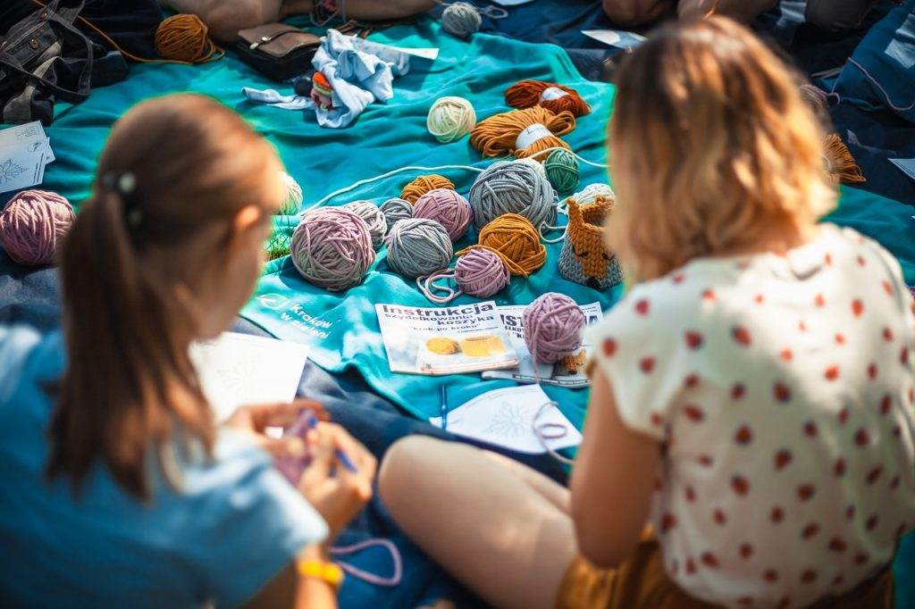 dziewczyny czytające instrukcje robienia na drutach