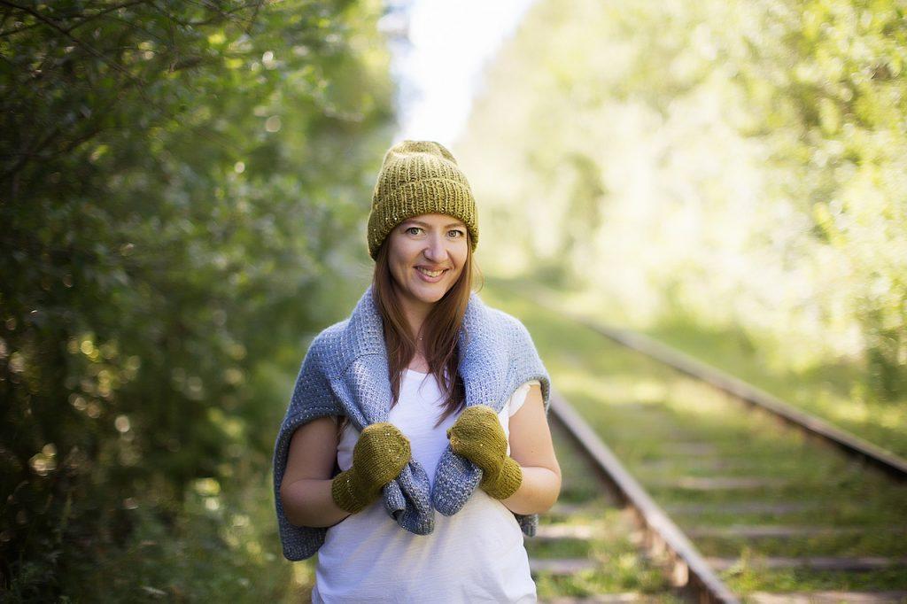 kobieta w czapce, swetrze i rękawiczkach wykonanych na drutach